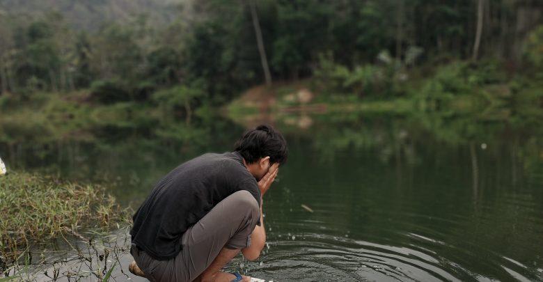 Membersihkan muka dengan air di alam terbuka