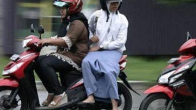 Perempuan pengendara sepeda motor dengan rok panjang
